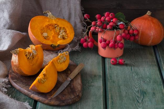 Abóboras e uma abóbora em uma placa de madeira no corte e uma faca, na caneca laranja encontra-se o hawthorn
