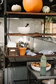 Abóboras e utensílios de cozinha em uma prateleira de madeira