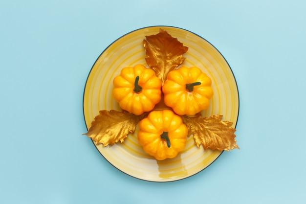 Abóboras em um prato amarelo na turquesa pastel.