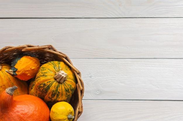 Abóboras em uma cesta de vime em um fundo de madeira branco natural, fundo de outono