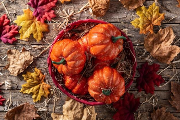 Abóboras em uma cesta vermelha em uma mesa de madeira rústica com folhas de outono