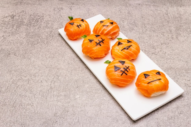 Abóboras engraçadas do sushi do dia das bruxas jack o lantern, monstro do sushi. sushi temari, bolas de sushi. comida saudável para crianças