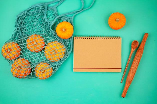Abóboras laranja brilhantes em saco de malha e o bloco de notas vazio para lista de compras ou receita