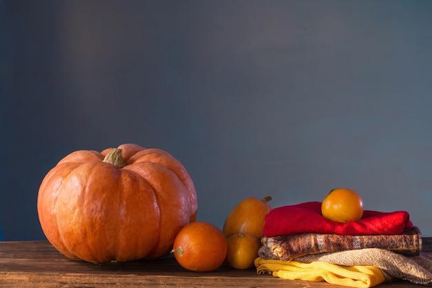 Abóboras laranja com folhas de outono na mesa de madeira