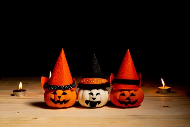 Abóboras laranja e brancas com velas sobre fundo preto.