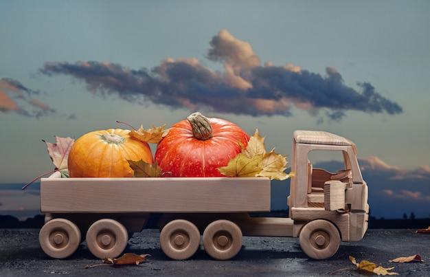 Abóboras laranja e folhas secas de bordo em um caminhão de brinquedo de madeira.