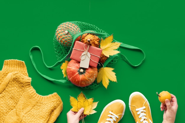 Abóboras laranja em saco de malha, folhas de plátano, mãos femininas no suéter de lã e um par de tênis de lona.