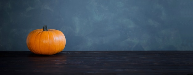 Abóboras laranja na mesa de madeira escura