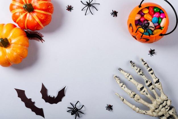 Abóboras, morcegos, braço de esqueleto e doces em cinza.