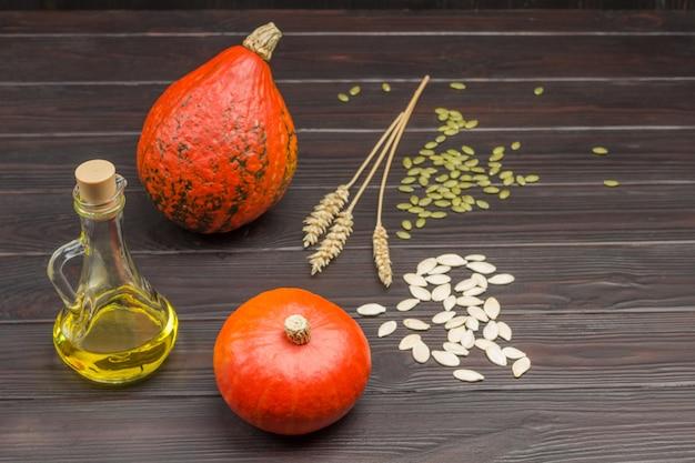 Abóboras, óleo em garrafa e sementes na mesa. raminhos de trigo. fundo de madeira.
