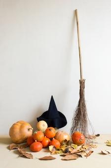 Abóboras, vassoura, chapéu de bruxa no fundo da parede branca