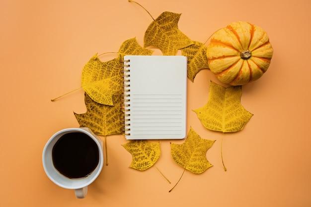 Abóboras, xícara de café e folhas caídas na laranja