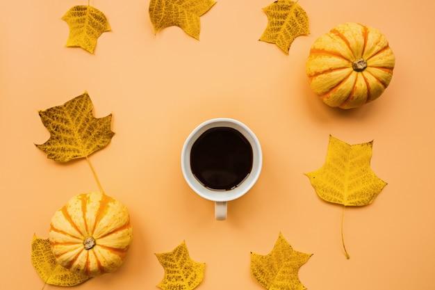 Abóboras, xícara de café e folhas caídas