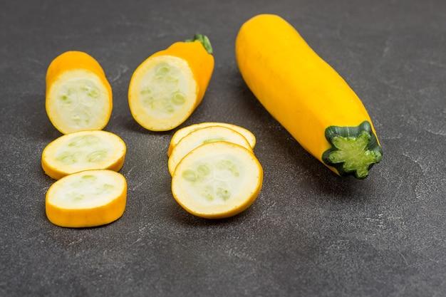 Abobrinha amarela madura, abobrinha fatiada, meio limão. fundo preto. vista do topo