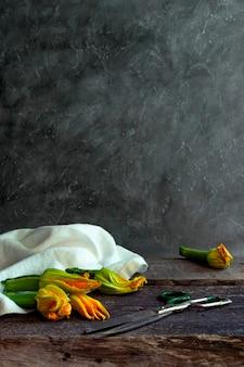 Abobrinha com flores e tesouras na velha mesa de madeira. copie o espaço