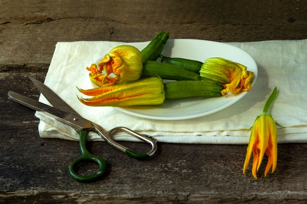 Abobrinha com flores e tesouras na velha mesa de madeira