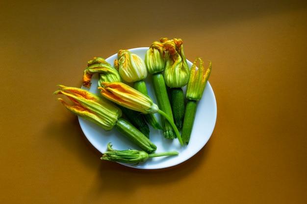 Abobrinha com flores em chapa branca sobre fundo marrom caramelo. camada plana, vista superior. copie o espaço