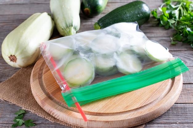 Abobrinha congelada em um saco plástico na mesa de madeira. conceito de alimentos congelados