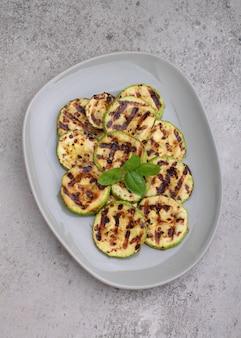 Abobrinha cortada em fatias e grelhada frita. decorado com manjericão.