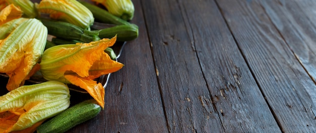 Abobrinha e flores de abobrinha em uma mesa de madeira