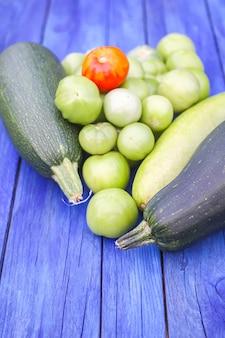 Abobrinha e tomates verdes. legumes orgânicos crus frescos em tábuas de madeira ao ar livre.