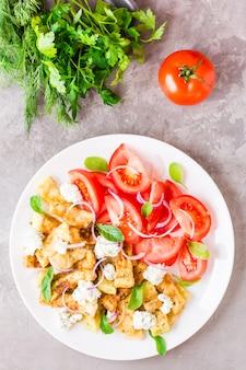 Abobrinha frita com queijo feta, tomate, ervas e cebola em um prato
