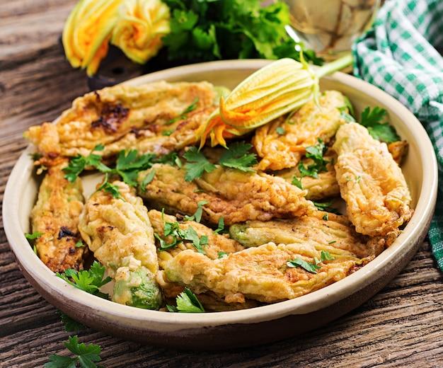 Abobrinha frita flores recheadas com ricota e ervas verdes. comida vegana. cozinha italiana.