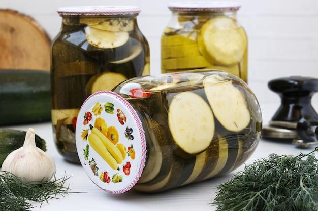 Abobrinha marinada em potes de vidro colocados sobre a mesa, close-up, orientação horizontal, colhendo vegetais para o inverno