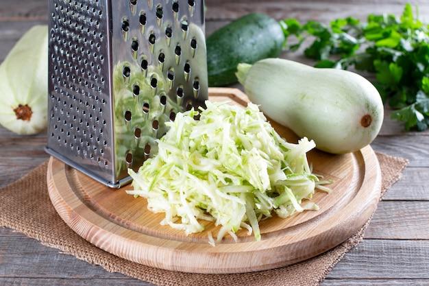 Abobrinha ralada com ralador a bordo na mesa de madeira. ingrediente vegetariano saudável