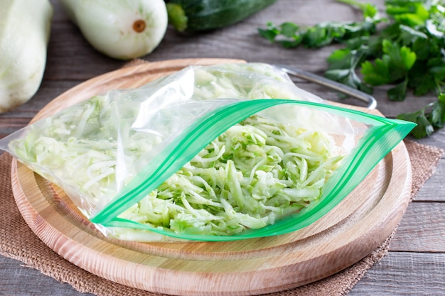 Abobrinha ralada em um saco plástico pronto para ser congelado em uma mesa de madeira. alimentos congelados conce