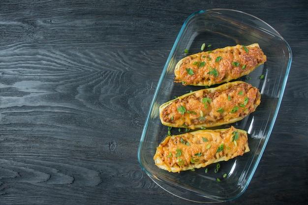 Abobrinha recheada com carne picada e queijo ralado em uma assadeira de vidro. fundo de madeira escuro. alimento saudável do equilíbrio.