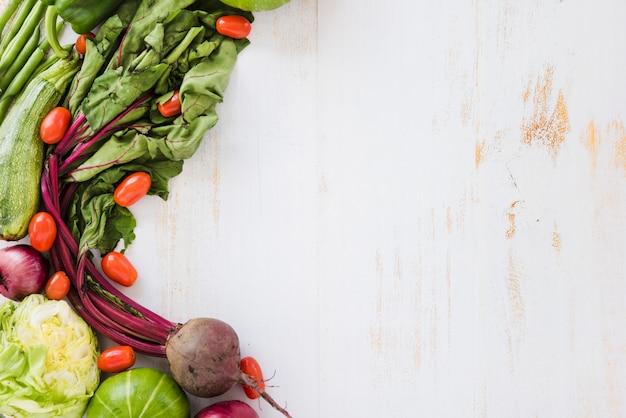 Abobrinha; tomates; repolho; cabaça e beterraba na mesa de madeira branca