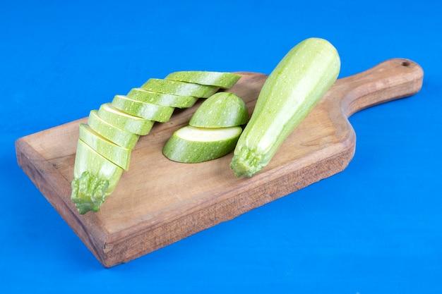 Abobrinha verde fresca e fatias colocadas na placa de madeira.