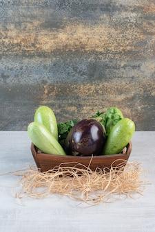 Abobrinhas e berinjelas cruas em caixa de madeira. foto de alta qualidade