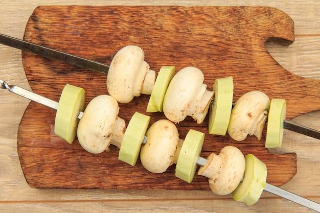 Abobrinhas e cogumelos em espetos. cogumelos e tutanos vegetais estão prontos para grelhar com espetos de metal. vista do topo