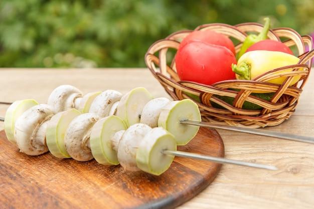 Abobrinhas e cogumelos no espeto com tomate, pepino e pimentão em uma cesta de vime. cogumelos e tutanos vegetais estão prontos para grelhar com espetos de metal.