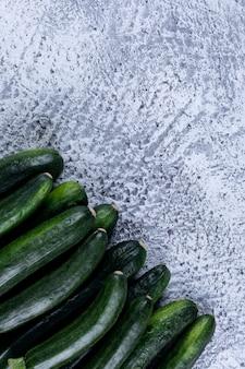 Abobrinhas frescas de vista superior na mesa texturizada cinza.
