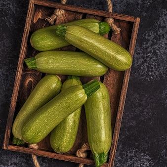 Abobrinhas verdes frescas e saudáveis em caixa de madeira marrom