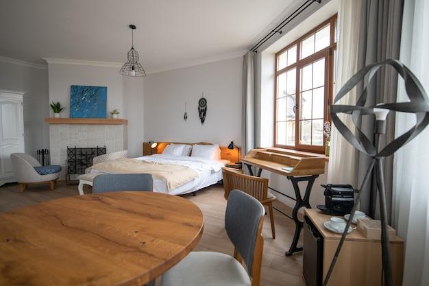 Abordagem de design. quarto de design espaçoso e bem iluminado com cama grande branca, lareira e itens de decoração
