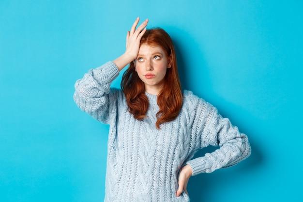 Aborrecida e cansada adolescente ruiva revirar os olhos, palma da mão e suspirando incomodada, parada em um suéter contra um fundo azul.