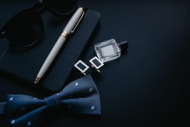 Abotoaduras masculinas de luxo com caneta e óculos em fundo escuro.