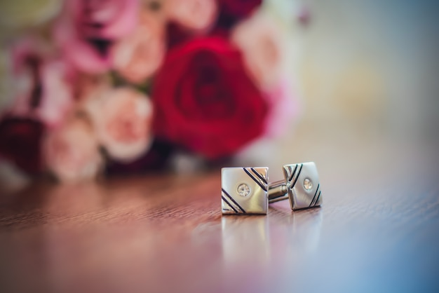 Abotoaduras para mangas ao lado do buquê de casamento