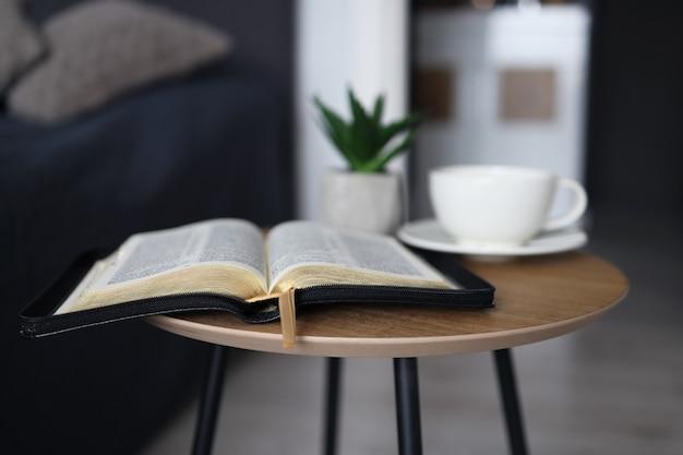 Abra a bíblia com uma xícara de chá em uma mesa de madeira no quarto. é hora de orar.