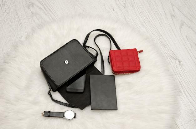Abra a bolsa preta com as coisas caídas, notebook, celular, relógio e bolsa vermelha.