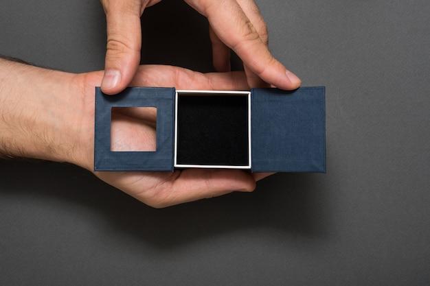 Abra a caixa de joia preta vazia nas mãos masculinas. presente.