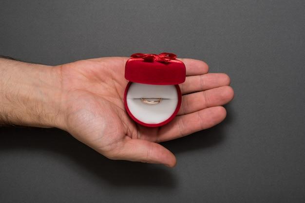 Abra a caixa de jóias vermelha com anel em uma palma masculina. presente. fundo preto
