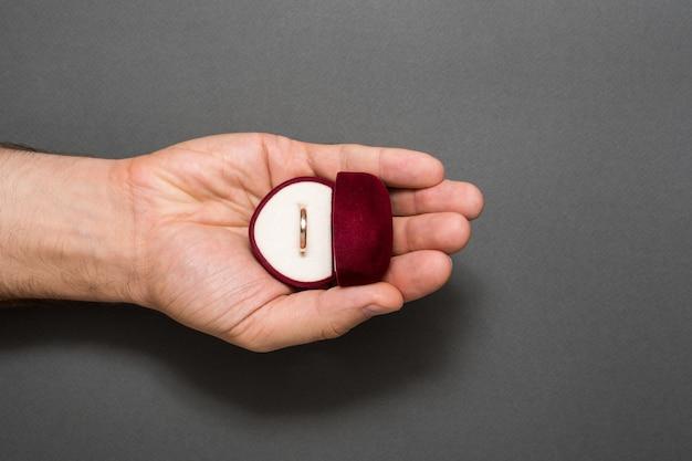 Abra a caixa de jóias vermelha com anel em uma palma masculina.