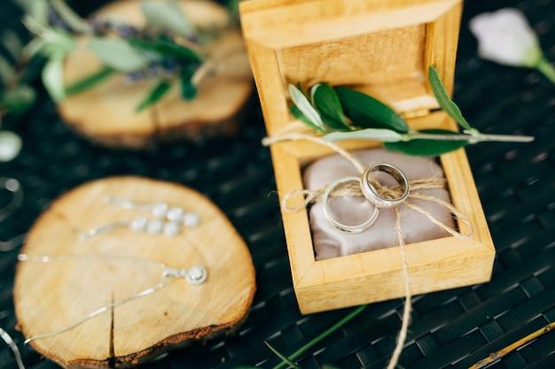 Abra a caixa de madeira com anéis de casamento e um suporte de madeira com brincos