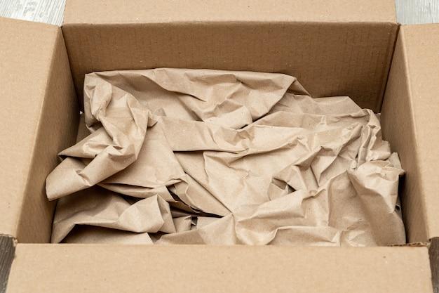 Abra a caixa de papelão cheia de papel de embrulho de perto