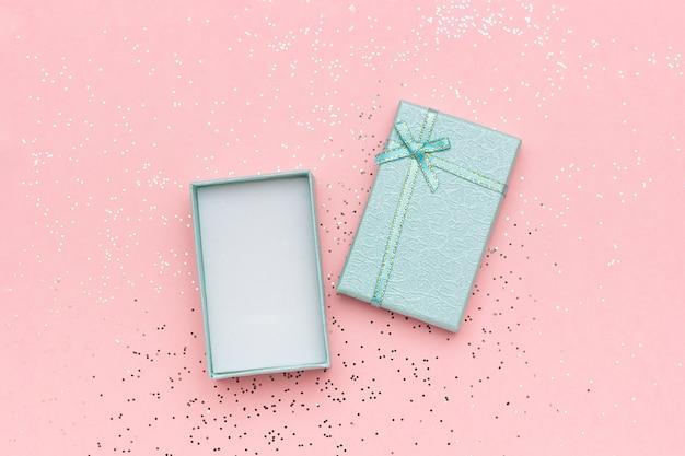Abra a caixa de presente azul com laço no pastel rosa
